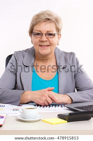 Elderly senior business woman working with financial chart at her desk in office, business concept, analysis of sales plan