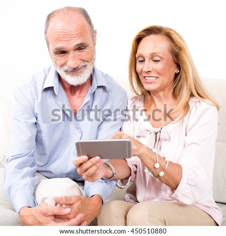 elderly senior couple looking together at a phone - stock photo