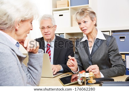 Elderly senior woman at communication over financial issues in a bank - stock photo