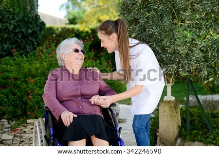 elderly senior woman on wheelchair with nurse outdoor in nursing home hospital garden - stock photo