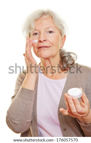 Elderly senior woman putting skin care lotion on her face - stock photo