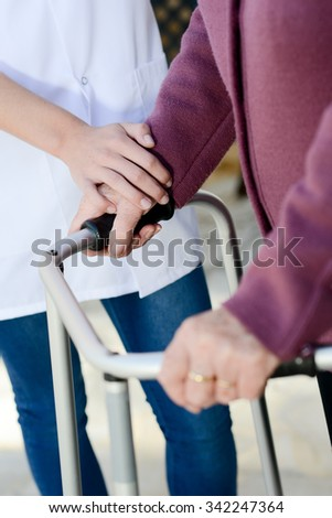 elderly senior woman with nurse hands detail - stock photo