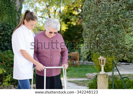 elderly senior woman with nurse walking outdoor in nursing home hospital garden