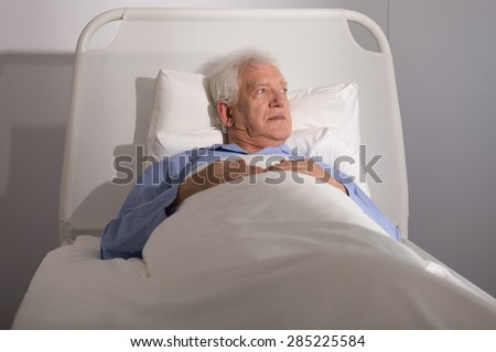 Elderly sick male patient lying in hospital bed - stock photo