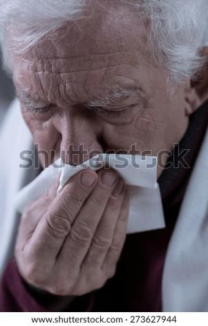 Elderly sick man blowing his rainy nose - stock photo