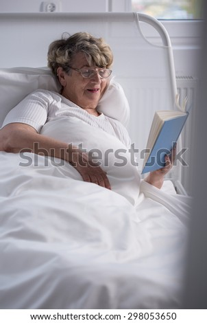 Elderly sick woman in hospital bed reading book - stock photo