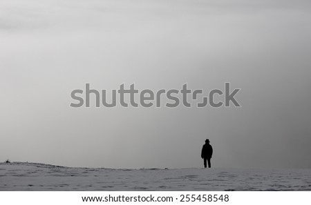 elderly silhouetted man in winter landscape above fog  - stock photo