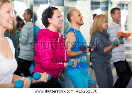 Elderly smiling people do pilates in a sport club with dumbbells