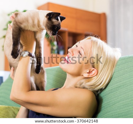 Elderly smiling woman playing with Siamese kitten on couch at home - stock photo