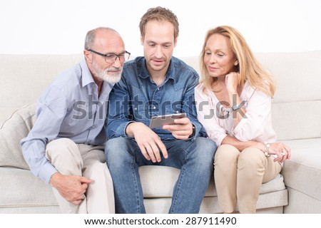 Elderly son looks at a phone with his parents - stock photo