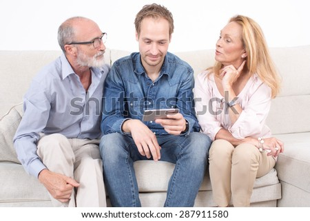 Elderly son shows something on a phone to his parents - stock photo