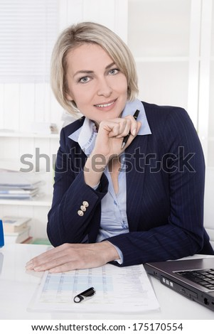 Elderly successful smiling female manager sitting at desk.