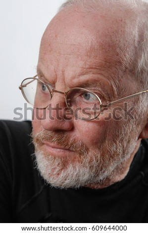 Elderly, Swedish man, with beard looking away from the camera looking quite serious.