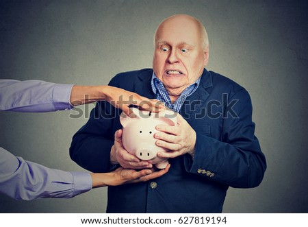 Elderly upset scared business man holding piggy bank trying to protect his savings from being stolen isolated gray background