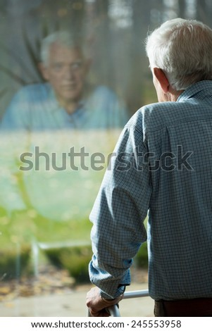 Elderly weak man looking through the hospital window - stock photo