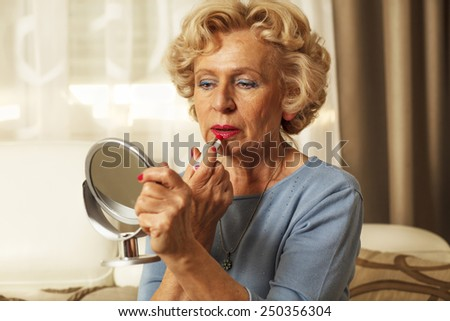 Elderly woman applied lipstick and looked in the mirror. - stock photo