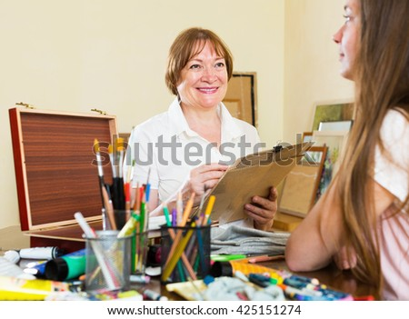 Elderly woman artist in the process of creating a new picture - stock photo