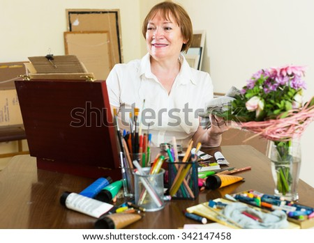 Elderly woman artist in the process of painting a new picture - stock photo