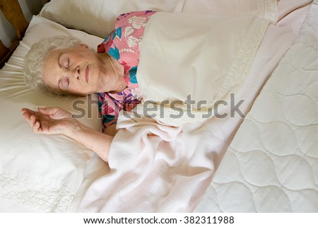 Elderly woman asleep in bed - stock photo