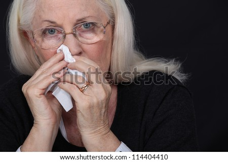 Elderly woman blowing her nose - stock photo