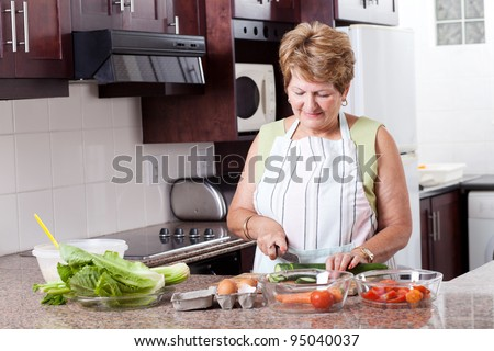 elderly woman cooking food in home kitchen - stock photo