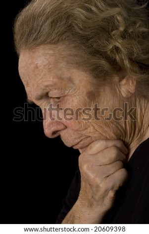 Elderly woman deep in thought on a black background. - stock photo