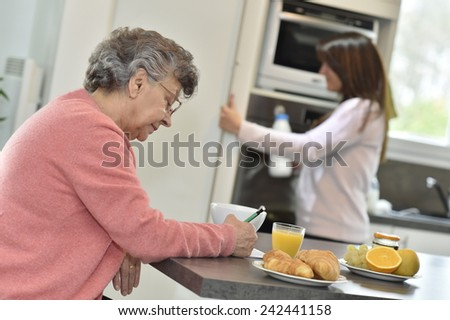 Elderly woman doing crossword while homecarer helps at home - stock photo