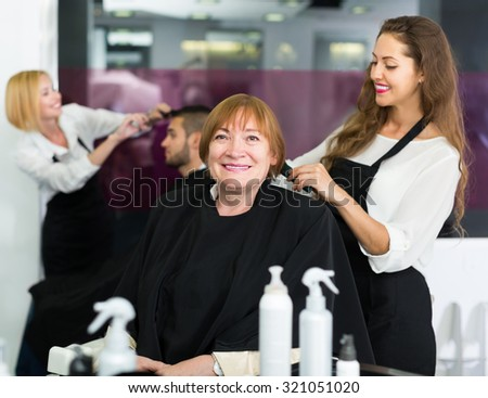 Elderly woman doing haircut  with girl hairstylist at the hair salon - stock photo