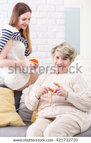 Elderly woman doing knitwork accompanied by her granddaughter