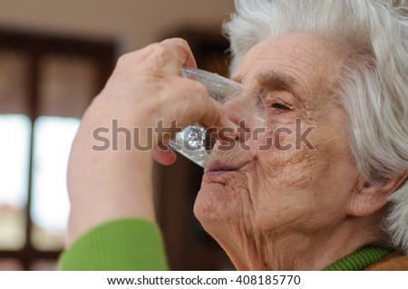Elderly woman drinking water from a glass - stock photo