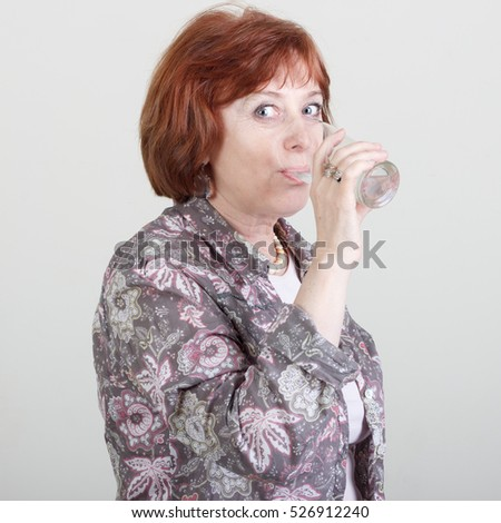 Elderly woman drinking water from a glass.