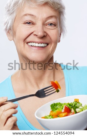 Elderly woman eating salad on white background - stock photo