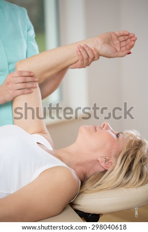 Elderly woman exercising at female physiotherapist's office - stock photo