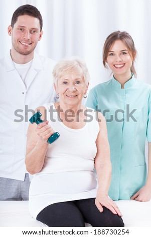 Elderly woman exercising with dumbbell in assist of therapists