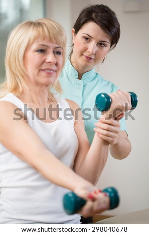 Elderly woman exercising with dumbbells at physiotherapist's office - stock photo