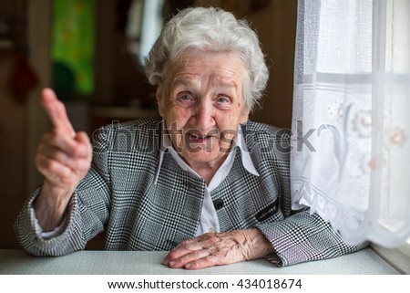 Elderly woman gesturing while sitting at the table. - stock photo