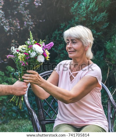 Elderly woman get a beautiful bouquet of field flowers. Smiling senior lady holding a bunch of flowers.  Close up of senior's hands holding a posy.