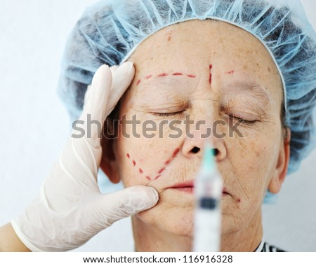 Elderly woman getting Botox injection surgery operation - stock photo