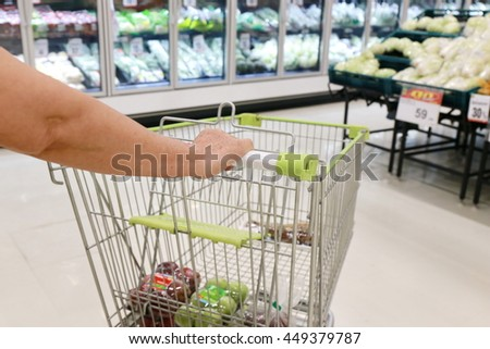 elderly woman hand push shopping cart handle in supermarket , abstract blurred photo of store with trolley in department store blurred background, retail and shopping mall business.