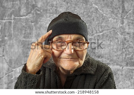 Elderly woman has an idea, pointing with finger on her head. - stock photo