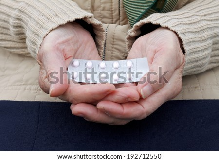 Elderly woman holding a medicament in her palm - stock photo