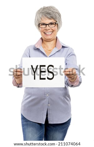 Elderly woman holding a paper card  with the word Yes - stock photo