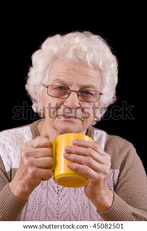elderly woman holding coffee or tea cup over black background