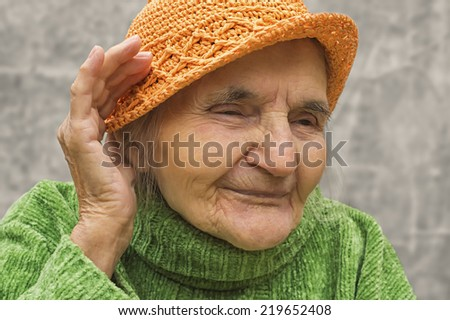Elderly woman holding hand close to an ear. Hearing problems. - stock photo
