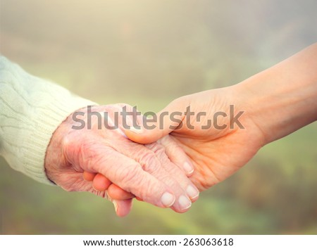 Elderly woman holding hands with young woman - stock photo