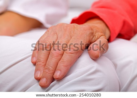 Elderly woman holding her aged and wrinkled hand - stock photo