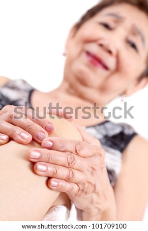 Elderly woman holding the knee with pain.