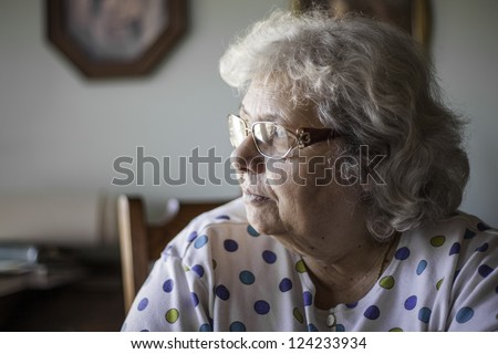 elderly woman in natural setting in the home. Shallow depth of field blurring the background. Look of thought or a feeling of loneliness.