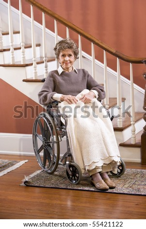 Elderly woman in 70s at home sitting in wheelchair - stock photo