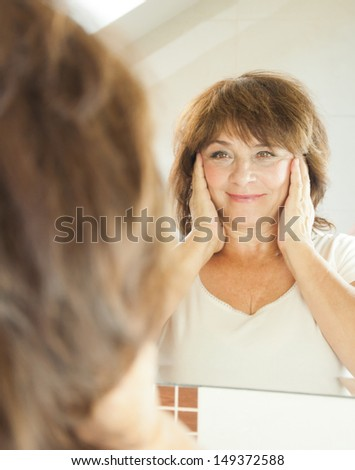 Elderly woman in the bathroom. - stock photo